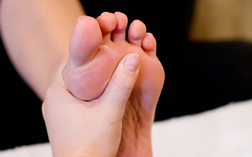 Benefits of regular reflexology foot massage include improved posture and increased circulation