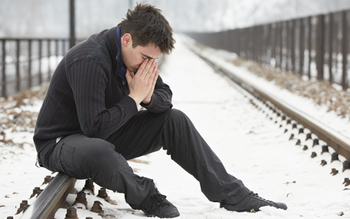 Man with seasonal affective disorder sitting on railroad track